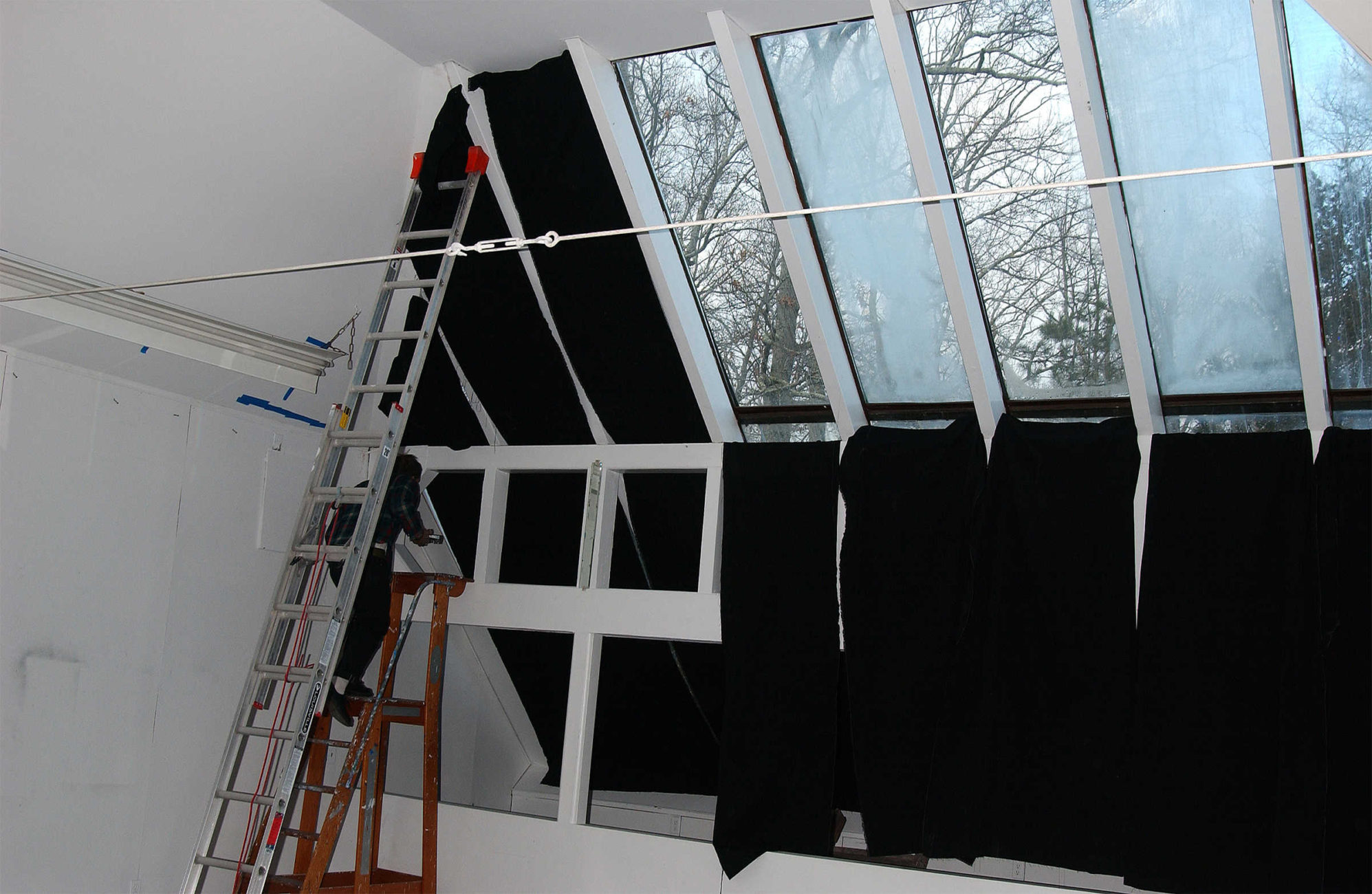 Artist Chris Duncan in residence at the historic and former home and studio of the painter Elaine de Kooning in East Hampton, NY.  The artist  places black cloth on the skylight of the studio to be bleached by the sun for a duration of four months. This effect is similar to that of a sungram or a solar etching.