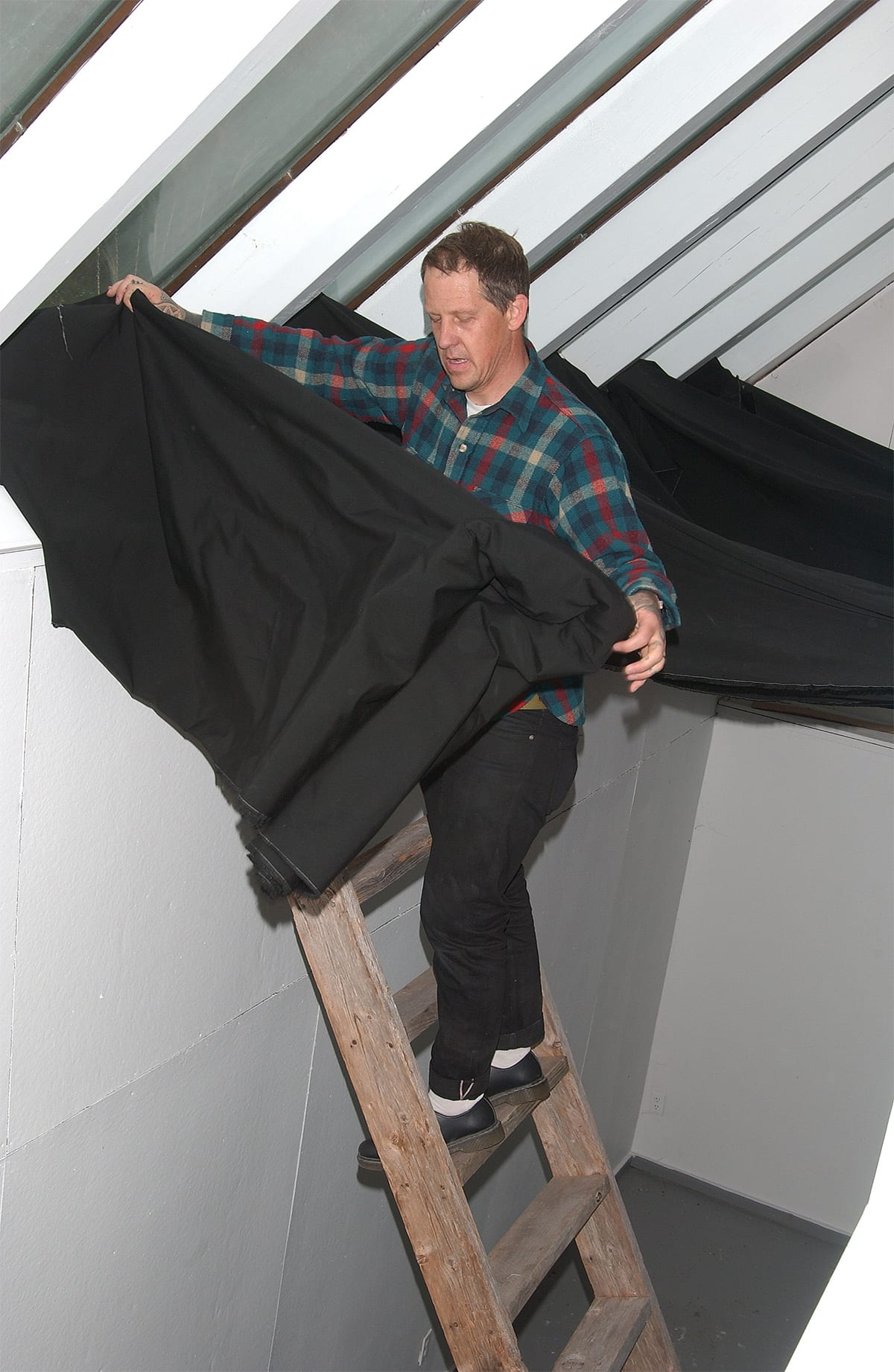 Artist Chris Duncan in residence at the historic and former home and studio of the painter Elaine de Kooning in East Hampton, NY.  The artist  places black cloth on the skylight of the studio to be bleached by the sun for a duration of four months. This effect is similar to that of a sungram or a solar etching. Assisting the artist is the Director and Co-owner of the Halsey Mckay Gallery, Ryan Wallace who is holding the ladder.