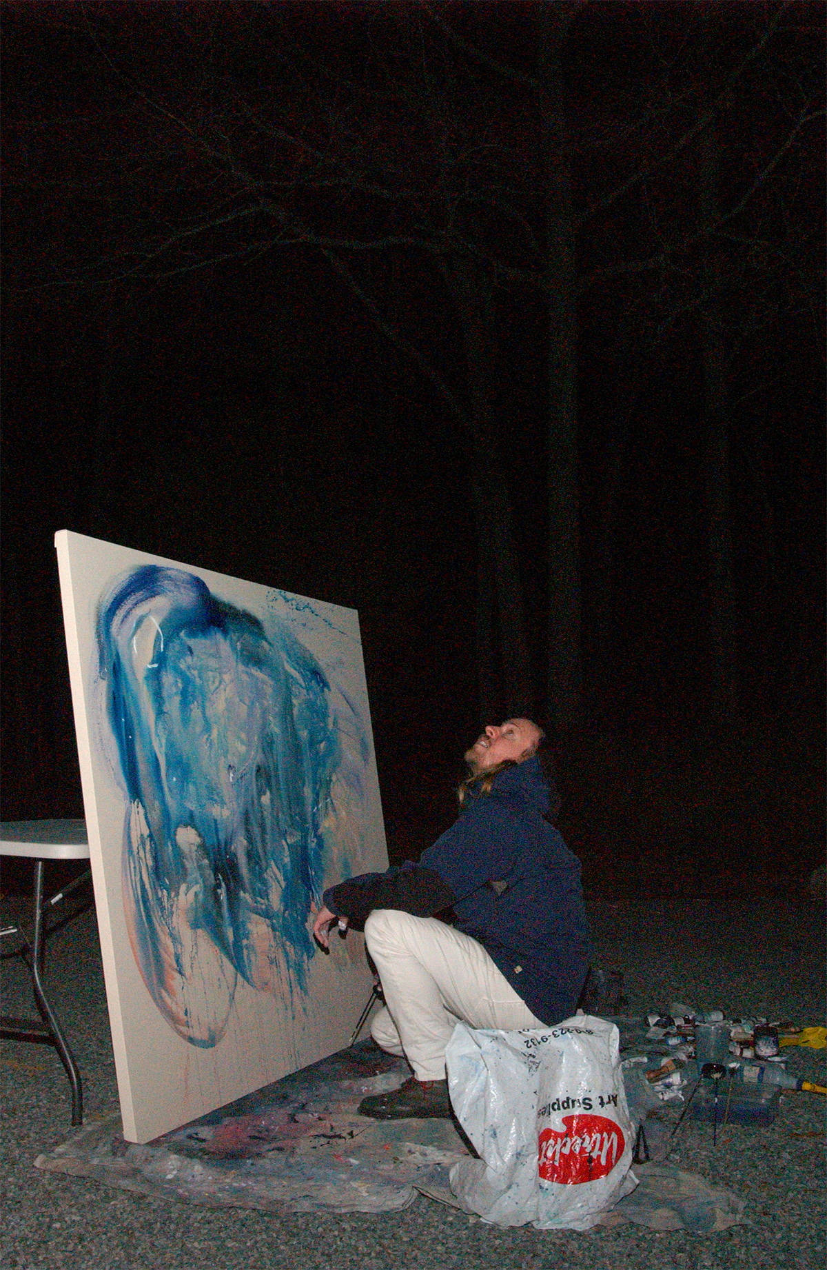 Artist and Art Dealer John Riepenhoff paints outdoors at night at the historic house and art studio originally owned by Elaine deKoonig. Artists John Chamberlain and Richmond Burton have lived and worked here. The structure's additions has multiple entrances and decks. The current owner an art curator makes this site available to other artists on a rotating basis which is located in the Northwest Woods of East Hampton, NY.
