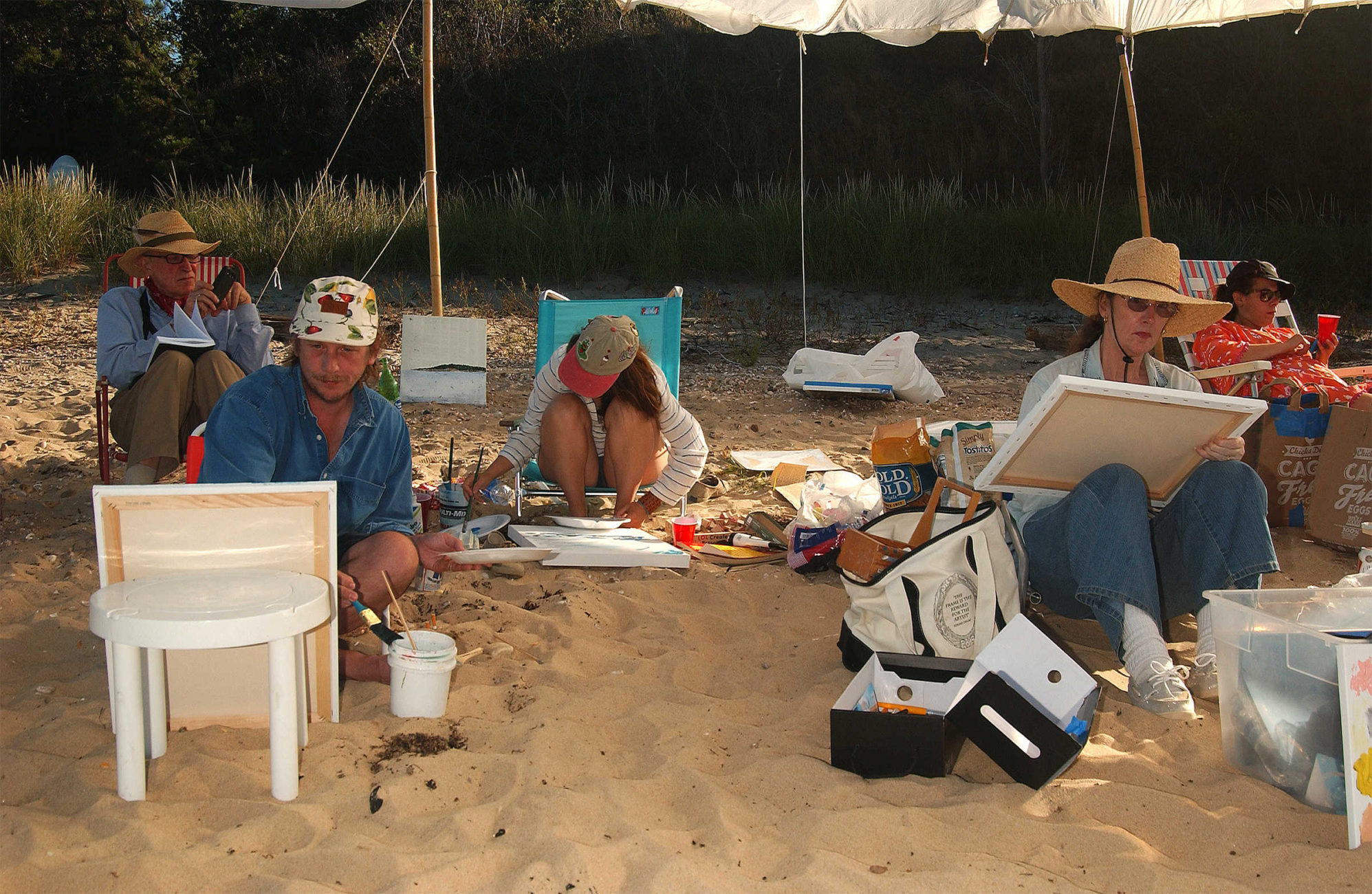 Artist Alex Wolfe (R) and artist Scott Reeder (L) participate with the Beach Painting Club at Sammy's Beach in East Hampton, New York.